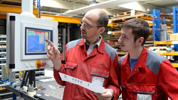 Un aprendiz alemán atiende a las explicaciones de su superior en una empresa metalúrgica