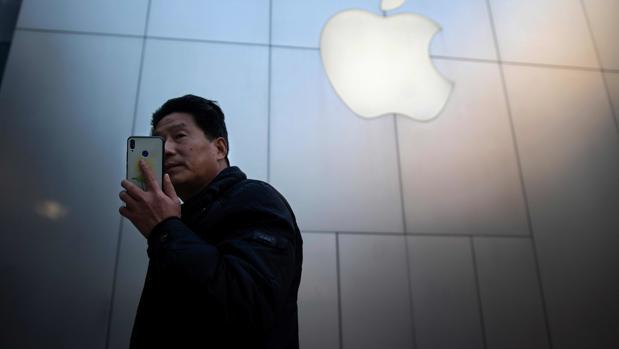 Un ciudadano, junto a la tienda de Apple en la capital china