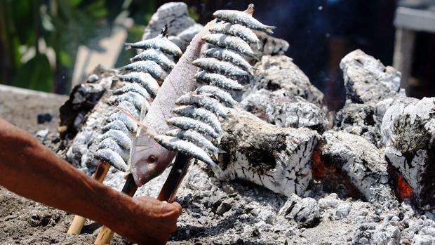 Un espetero preprara unas sardinas en un chiringuito de Málaga