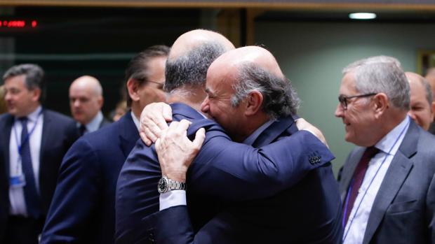 El vicepresidente del BCE, Luis de Guindos, se abraza al comisario de Asuntos Económicos, Pierre Moscovici