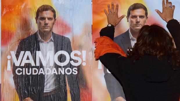 Una simpatizante de Ciudadanos pega carteles electorales en Valladolid