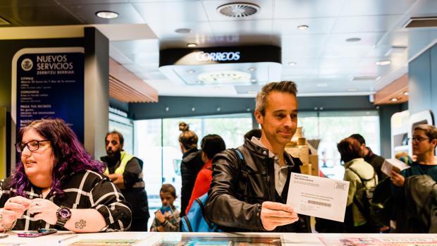 Personas gestionando el voto por correo en una oficina de Correos