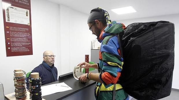 Un joven recoge su «compostela» en el nuevo Centro internacional de acogida al peregrino de Santiago