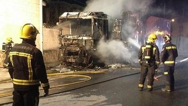 Los bomberos intentan apagan las llamas del camión