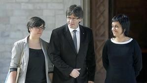 El presidente de la Generalitat Joan Puigdemont con las representantes de la CUP, Mireia Boya (i) y Anna Gabriel