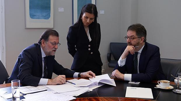 Mariano Rajoy muestra las cifras de la evolución económica de España a Bieito Rubido, director de ABC, y a Montserrat Lluis, subdirectora, al final de la entrevista