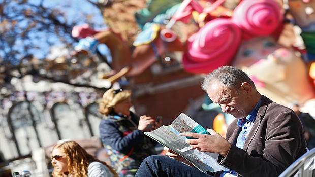 Imagen de un turistas observando un plano de Valencia en una imagen tomada este viernes