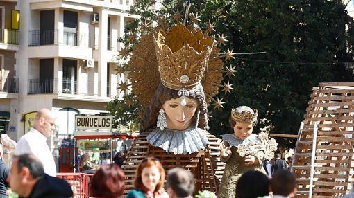 Unos turistas toman un refresco ante la imagen de la Virgen de los Desamparados