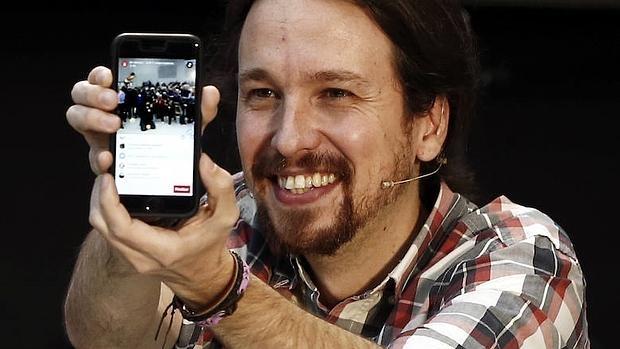 El secretario general de Podemos, Pablo Iglesias, con su móvil
