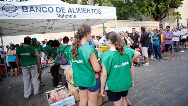 Cola de personas esperando en el reparto de alimentos, tomada en julio de 2015