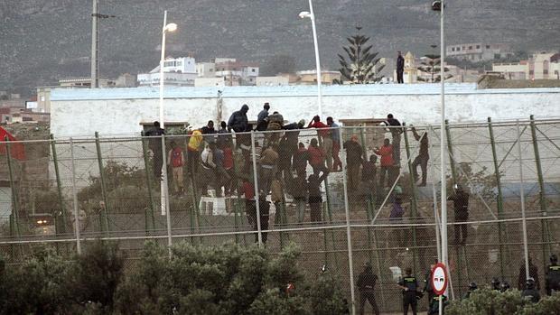 Imagen de 2014 de varios inmigrantes encaramados a la valla de Melilla