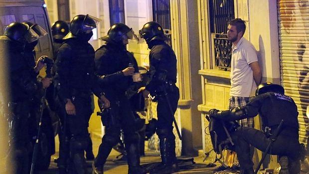 Miembros de los antidisturbios realizan un registro por las calles del barrio barcelonés de Gracia