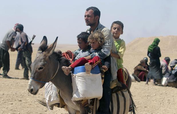 Refugiados sirios huyen por la frontera entre Siria e Irak