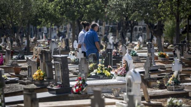 Dos vecinos visitan una lápida en el cementerio municipal de Valencia