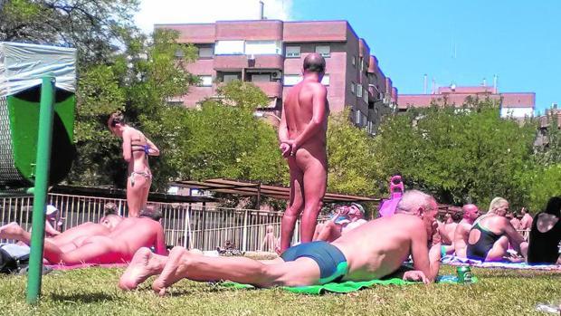 Nudistas y usuarios en bañador disfrutan de la piscina