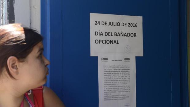 Una chica lee el cartel informativo que advierte del «Día del bañador opcional»