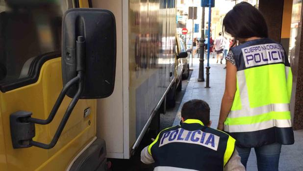 Dos agentes inspeccionan uno de los camiones a los que se robó la batería.
