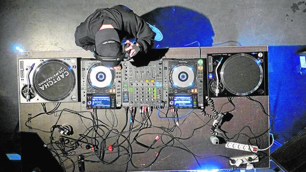 Un DJ selecciona y mezcla música en su equipo
