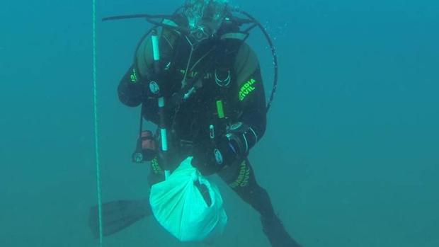 Un buceador de la Guardia Civil con restos hallados en el mar