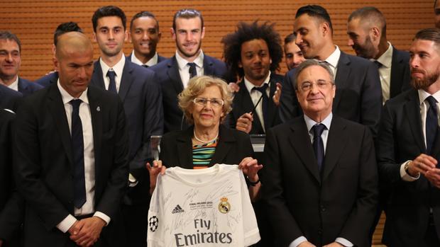 Manuela Carmena posa con una camiseta del Real Madrid junto a Florentino Pérez y la plantilla, tras ganas la Undécima