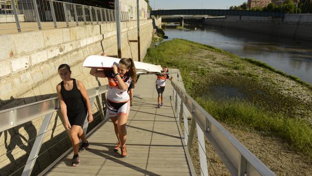 Varios alumnos de una escuela de remo sacan una barca del río, con el caudal a un nivel mínimo