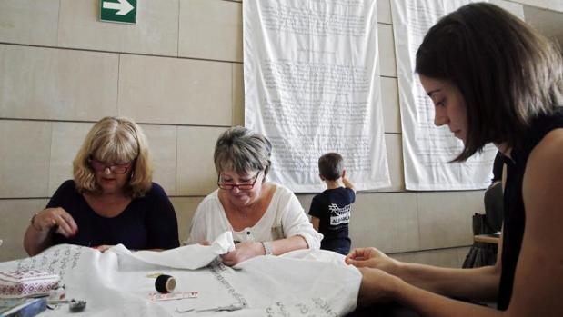 Varias voluntarias bordando la orden ministerial en la tela