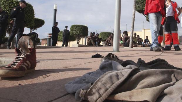 Los inmigrantes, al fondo de la imagen, que ayer llegaron a Melilla