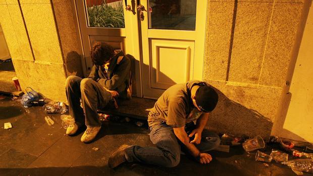 Dos jóvenes, rodeados de los restos de un botellón en una calle de La Coruña