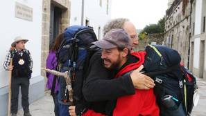 Dos peregrinos se abrazan tras terminar el Camino de Santiago