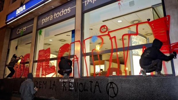 Grafiteros pintan el escaparate de una entidad bancaria en el centro de Valencia
