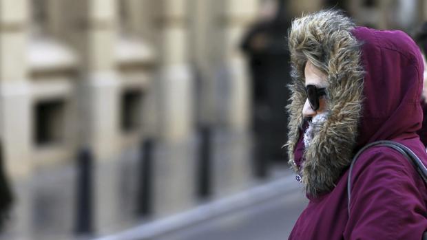 una mujer se protege del fro en valencia