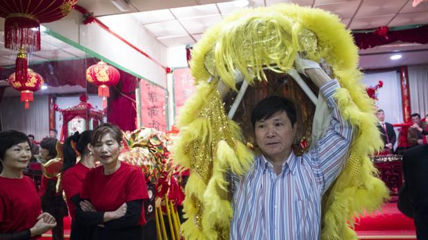 Un hombre se dispone a colocarse el traje de león para ensayar el desfile de la festividad del Año Nuevo Chino