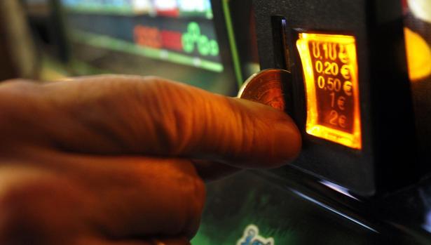 Un jugador echa una moneda en una máquina tragaperras