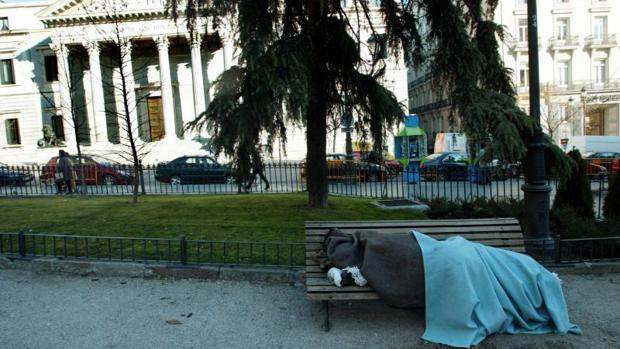 Una persona sin hogar duerme en un banco frente al Congreso de los Diputados