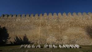 Cartel de la Villa del Libro junto a la muralla de Urueña