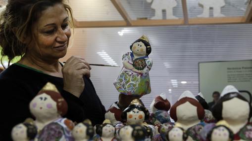 La artesana fallera Verónica Palomares, dan los últimos toques a sus falleras que luego venderá a turistas