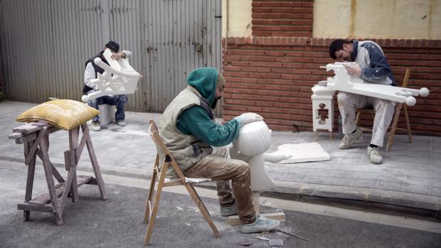 Varios operarios trabajan con piezas de una falla en la Ciudad del Artista Fallero