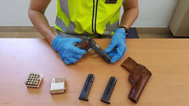 Imagen de un agente con la pistola incautada al fugitivo