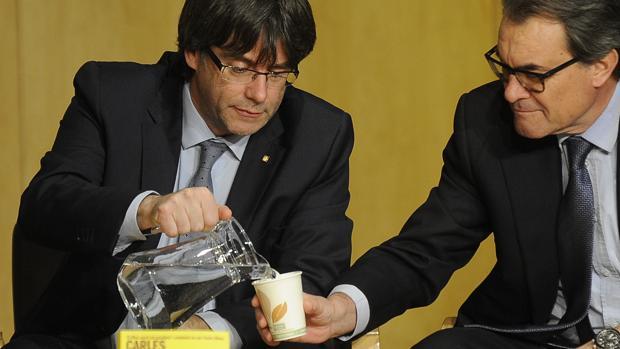 Carles Puigdemont, presidente de la Generalitat catalana, sirve agua a Artur Mas, en una imagen de archivo