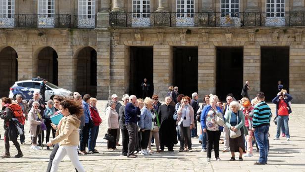 Un grupo de turistas atiende ayer las explicaciones de una guía en la plaza del Obradoiro de Santiago