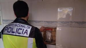 Un agente extrae cocaína escondida en una pared de la vivienda registrada