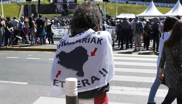 Una personas se cubre con una bandera a favor del acercamiento de los presos de ETA, en Bayona