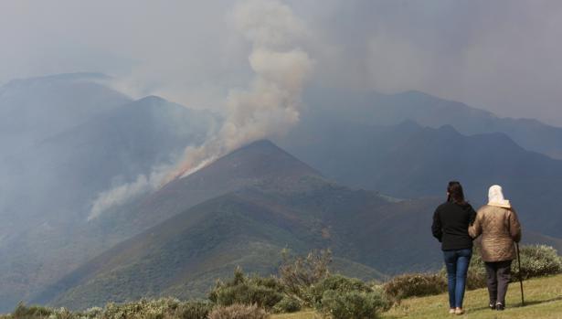 Dos personas contemplan el humo originado por el incendio en El Bierzo (León)