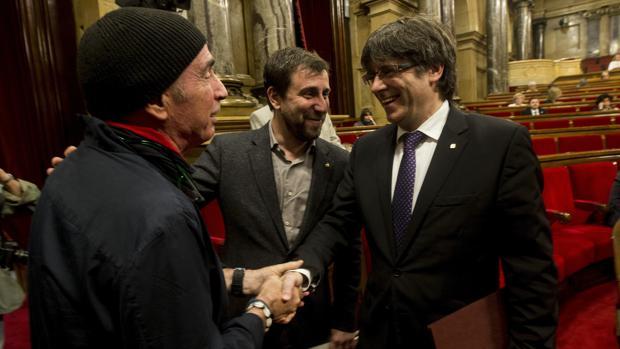 Lluís Llach saluda a Puigdemont en el Parlament