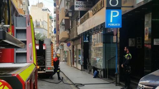 Un policía local y un bombero, trabajando por el fuego