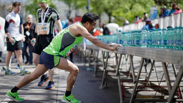 Un deportista hace ejercicios de estiramiento frente a una de las mesas de avituallamiento de agua para hidratación de los deportistas