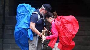 Dos peregrinos unen sus cabezas al llegar a la plaza del Obradoiro