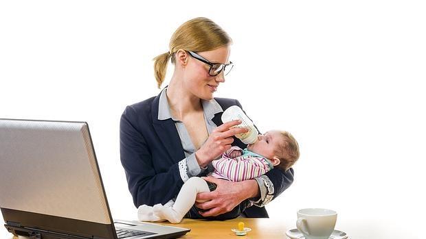 Una mujer da el biberón a su hijo delante de un ordenador de trabajo