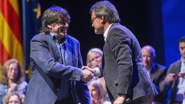 Puigdemont y Mas se dan la mano durante la I conferencia ideológica del partido