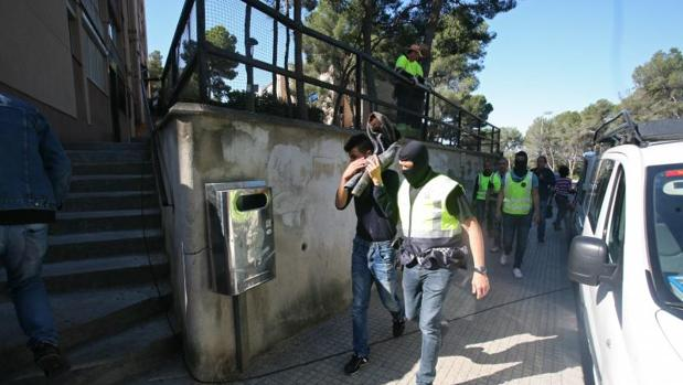 Miembros de los Mossos, con uno de los detenidos esta mañana en Tarragona